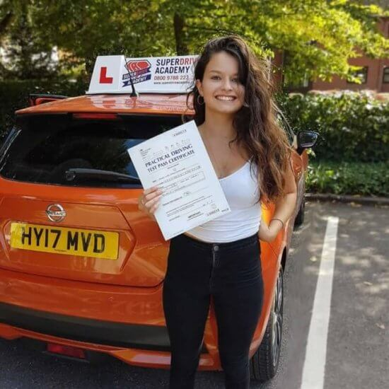Young women with her driving test pass certificate after passing the driving test