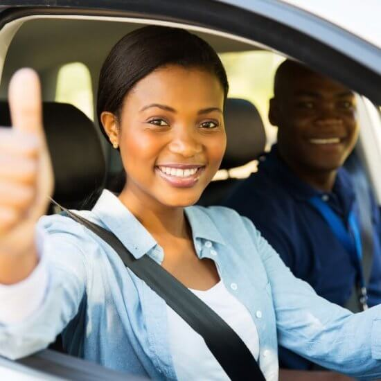 Young women learner driver having driving lesson with an approved driving instructor